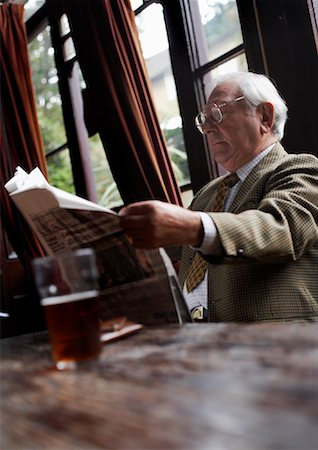 Man Reading Newspaper in Pub Stock Photo - Premium Royalty-Free, Code: 600-01123737