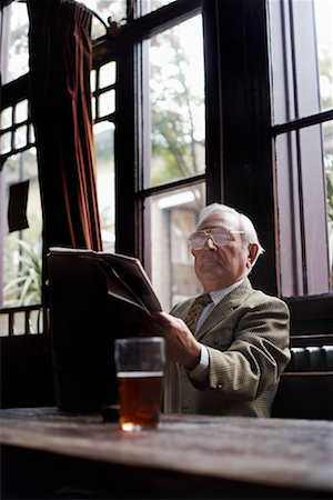 Man Reading Newspaper in Pub Stock Photo - Premium Royalty-Free, Code: 600-01123738
