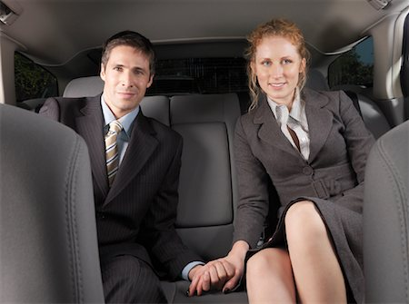 Man and Woman Holding Hands in Back of Car Stock Photo - Premium Royalty-Free, Code: 600-01173939