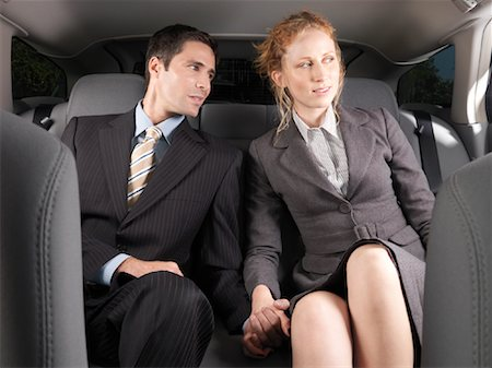 Man and Woman Holding Hands in Back of Car Stock Photo - Premium Royalty-Free, Code: 600-01173940