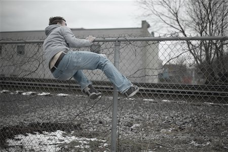 running away scared - Man Climbing over Fence Stock Photo - Premium Royalty-Free, Code: 600-01184409
