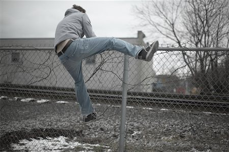 running away scared - Man Climbing over Fence Stock Photo - Premium Royalty-Free, Code: 600-01184410