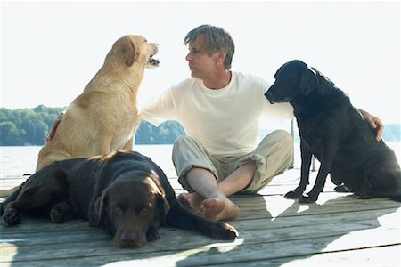 Man With Dogs, Sitting on Dock Stock Photo - Premium Royalty-Free, Code: 600-01183024