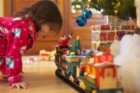Little Girl Looking at Toy Train Stock Photo - Premium Royalty-Free, Code: 600-01195006