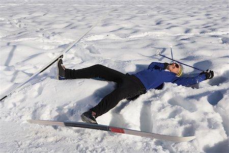 Man Wearing Skis, Lying in Snow Stock Photo - Premium Royalty-Free, Code: 600-01235201