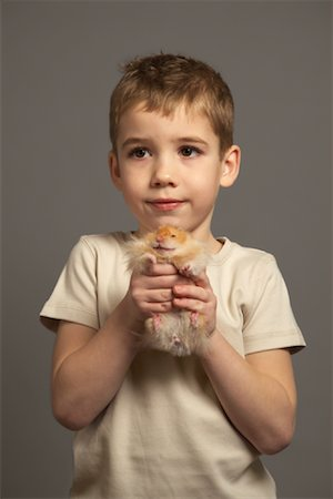 Little Boy Holding Hamster Stock Photo - Premium Royalty-Free, Code: 600-01275394