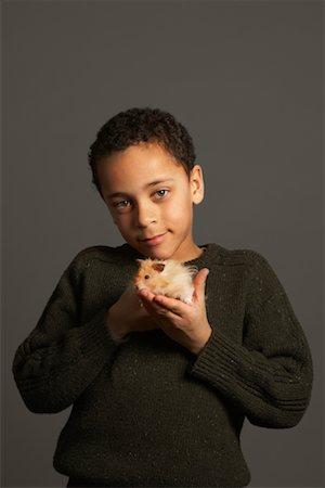 Little Boy Holding Hamster Stock Photo - Premium Royalty-Free, Code: 600-01275398
