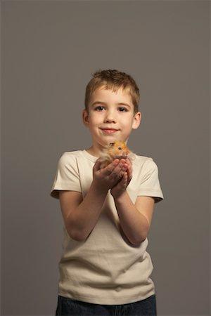 Little Boy Holding Hamster Stock Photo - Premium Royalty-Free, Code: 600-01275392