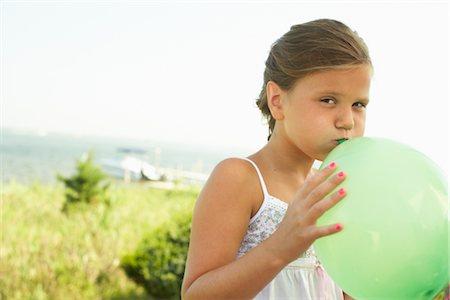 Girl Blowing Up Balloon Stock Photo - Premium Royalty-Free, Code: 600-01614153