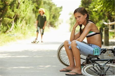 Little Girl Sitting on Bike Looking Angry Stock Photo - Premium Royalty-Free, Code: 600-01614189