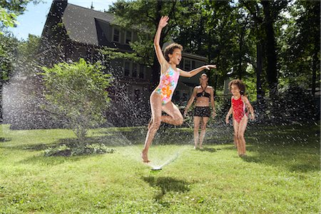 Family playing in backyard with sprinkler Stock Photo - Premium Royalty-Free, Code: 600-01614307