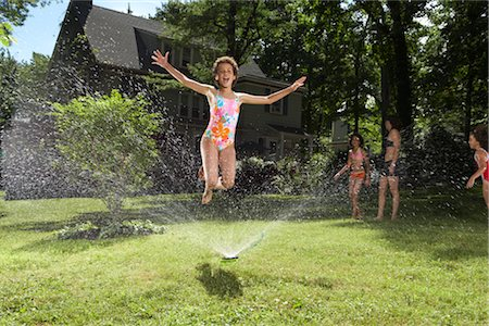 Family playing in backyard with sprinkler Stock Photo - Premium Royalty-Free, Code: 600-01614309