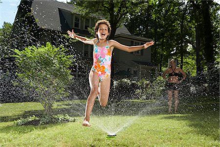 Family playing in backyard with sprinkler Stock Photo - Premium Royalty-Free, Code: 600-01614314