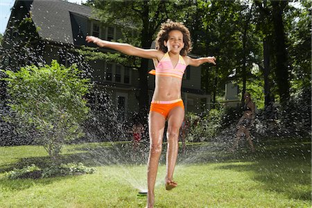 Family playing in backyard with sprinkler Stock Photo - Premium Royalty-Free, Code: 600-01614315