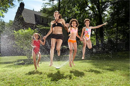 Family playing in backyard with sprinkler Stock Photo - Premium Royalty-Free, Code: 600-01614316