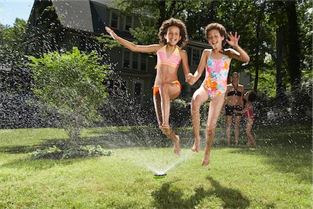 Family playing in backyard with sprinkler Stock Photo - Premium Royalty-Free, Code: 600-01614312