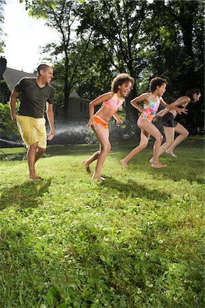 Family Playing in Backyard with Sprinkler Stock Photo - Premium Royalty-Free, Code: 600-01614321