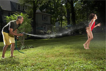 Father and Daughter Playing with Water Hose in Backyard Stock Photo - Premium Royalty-Free, Code: 600-01614322