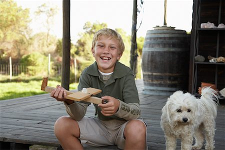 Portrait of Boy With Dog and Model Airplane Stock Photo - Premium Royalty-Free, Code: 600-01614640