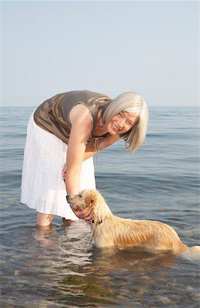 Woman Petting Dog in Water Stock Photo - Premium Royalty-Free, Code: 600-01616647
