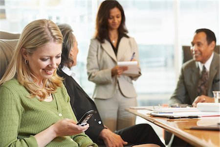 Businesswoman Using Her Cell Phone During Meeting Stock Photo - Premium Royalty-Free, Code: 600-01613744