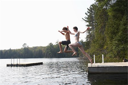 Couple Jumping from Dock Stock Photo - Premium Royalty-Free, Code: 600-01670945