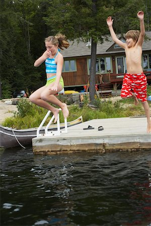 Boy and Girl Jumping off Dock Stock Photo - Premium Royalty-Free, Code: 600-01694208