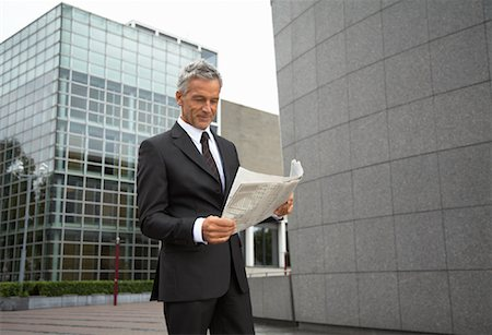 Businessman Reading Newspaper, Amsterdam, Netherlands Stock Photo - Premium Royalty-Free, Code: 600-01695556