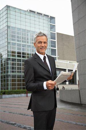 Businessman Reading Newspaper, Amsterdam, Netherlands Stock Photo - Premium Royalty-Free, Code: 600-01695558