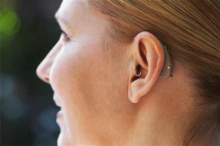 Close-up Of Woman's Ear with Hearing Aid Stock Photo - Premium Royalty-Free, Code: 600-01716099