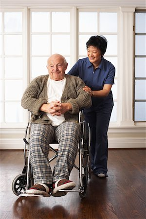 Senior Man Receiving Assistance with Wheelchair Stock Photo - Premium Royalty-Free, Code: 600-01716129