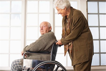 Senior Man Receiving Assistance with Wheelchair Stock Photo - Premium Royalty-Free, Code: 600-01716131