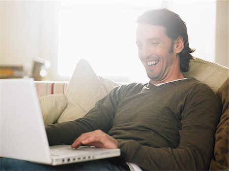 Portrait of Man Sitting on Sofa using Laptop Computer Stock Photo - Premium Royalty-Free, Code: 600-01742752