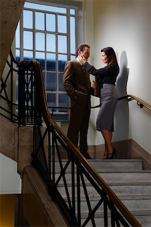 Businessman and Woman Flirting in Stairwell Stock Photo - Premium Royalty-Free, Code: 600-01742932