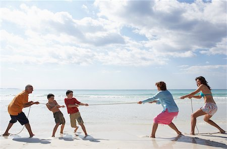 Family Playing Tug-of-War on the Beach Stock Photo - Premium Royalty-Free, Code: 600-01755533
