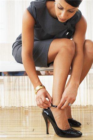 Woman Putting on Shoe Stock Photo - Premium Royalty-Free, Code: 600-01753614