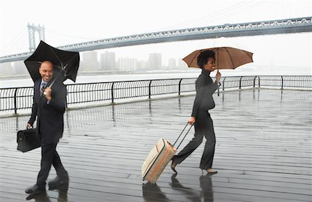 Business People Walking in Rain by Brooklyn Bridge, New York City, New York, USA Stock Photo - Premium Royalty-Free, Code: 600-01764138