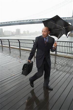 Business People Walking in Rain by Brooklyn Bridge, New York City, New York, USA Stock Photo - Premium Royalty-Free, Code: 600-01764139