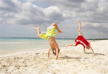 Boy and Girl doing Cartwheels on Beach, Majorca, Spain Stock Photo - Premium Royalty-Free, Code: 600-01764750