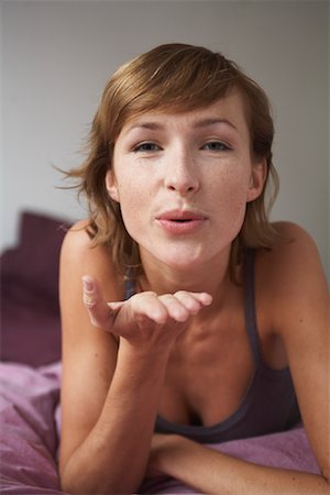 Woman in Bed Blowing Kiss Stock Photo - Premium Royalty-Free, Code: 600-01787394
