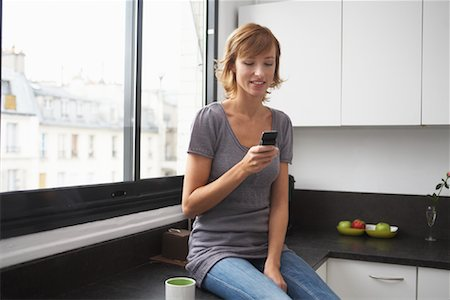 Woman in Kitchen with Cellular Phone, Paris, France Stock Photo - Premium Royalty-Free, Code: 600-01787413
