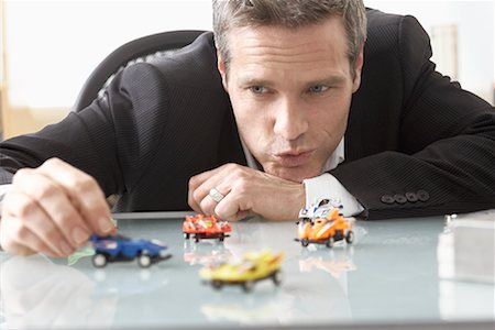 Businessman Playing with Toy Race Cars on Desk Stock Photo - Premium Royalty-Free, Code: 600-02081700