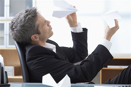 Businessman Playing with Paper Airplanes at Desk Stock Photo - Premium Royalty-Free, Code: 600-02081710