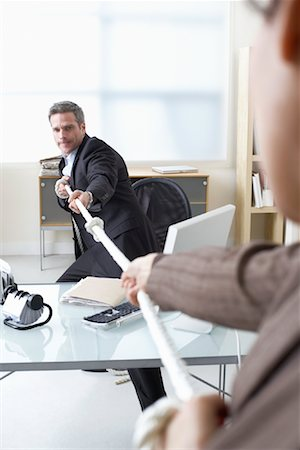 Business People in Tug-of-War at Desk Stock Photo - Premium Royalty-Free, Code: 600-02081759