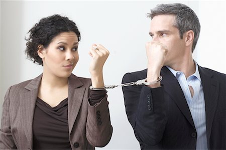 sad lovers break up - Businessman and Businesswoman Handcuffed Together Stock Photo - Premium Royalty-Free, Code: 600-02081774