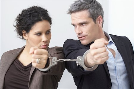sad lovers break up - Businessman and Businesswoman Handcuffed Together Stock Photo - Premium Royalty-Free, Code: 600-02081775