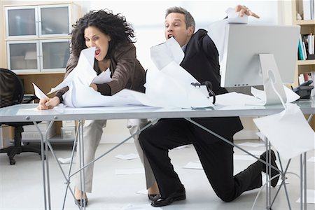 Business People Trying to Hold onto Paperwork Blowing Around on Desk Stock Photo - Premium Royalty-Free, Code: 600-02081778