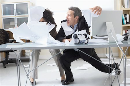 Business People Trying to Hold onto Paperwork Blowing Around on Desk Stock Photo - Premium Royalty-Free, Code: 600-02081779