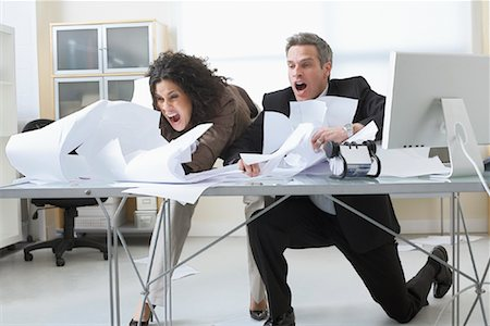 Business People Trying to Hold onto Paperwork Blowing Around on Desk Stock Photo - Premium Royalty-Free, Code: 600-02081784
