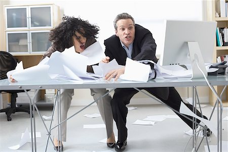 Business People Trying to Hold onto Paperwork Blowing Around on Desk Stock Photo - Premium Royalty-Free, Code: 600-02081780